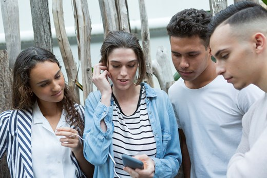 4 teenagers standing looking at the mobile phone of the middle girl